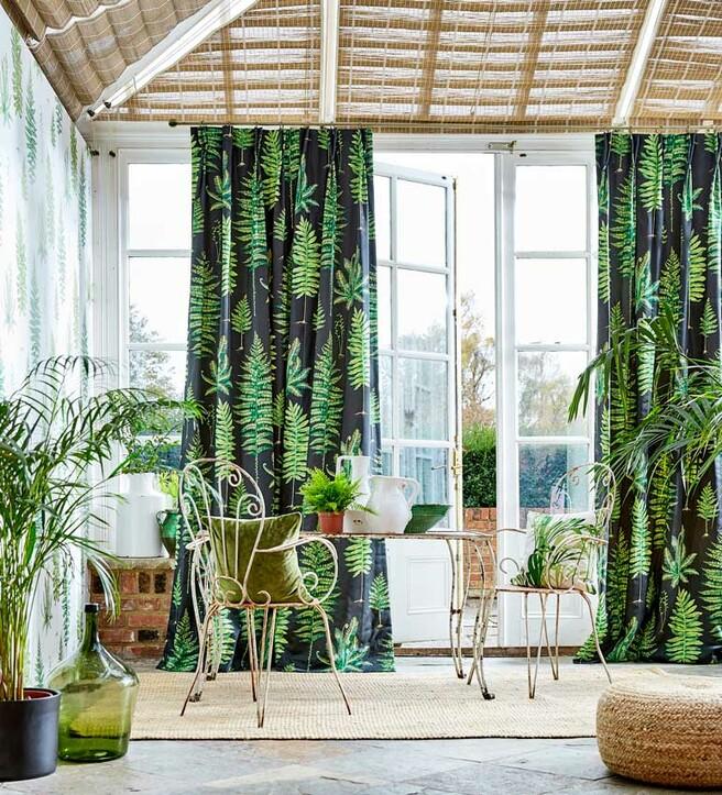Rincón del salón decorado con plantas y cortinas de estampado vegetal